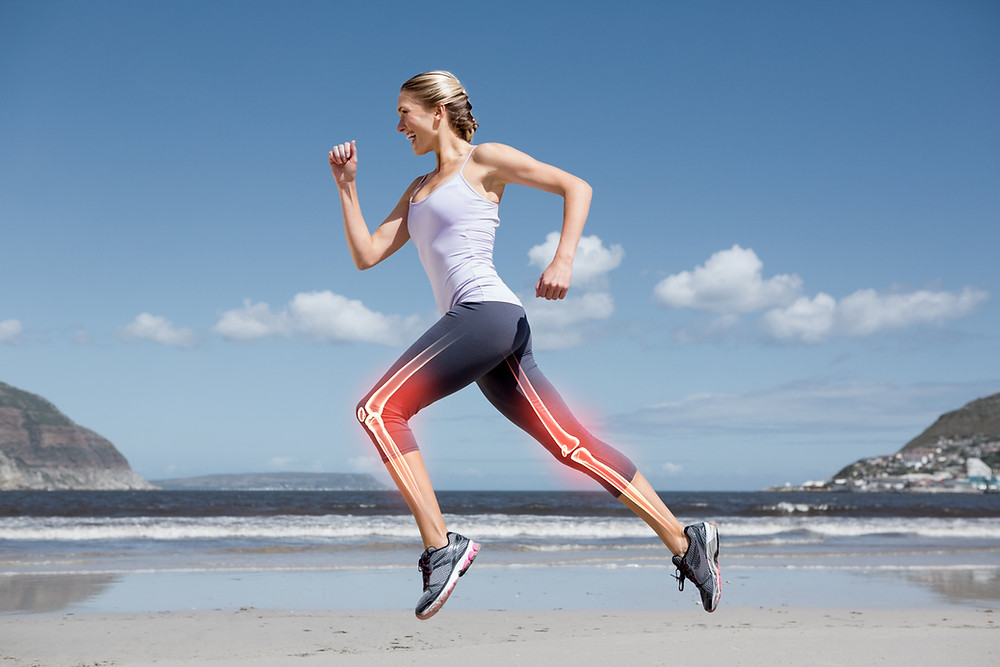 Young woman jumping in air wearing workout clothes on the beach. Woman's leg bones are highlighted. Strength training for bone density.