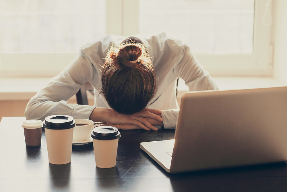 Young woman with head down at desk fatigued, sleeping at work after multiple coffees, fatigued at work