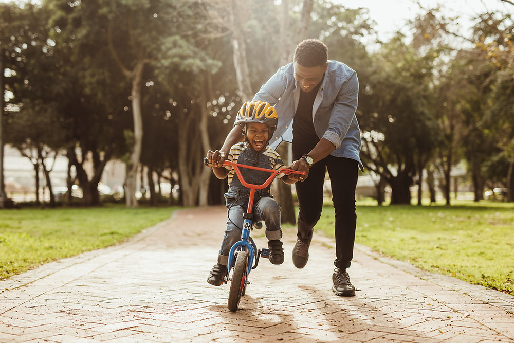 Father and son riding on bikes outside, enjoying some sunshine and exercise. Healthy lifestyle concept.