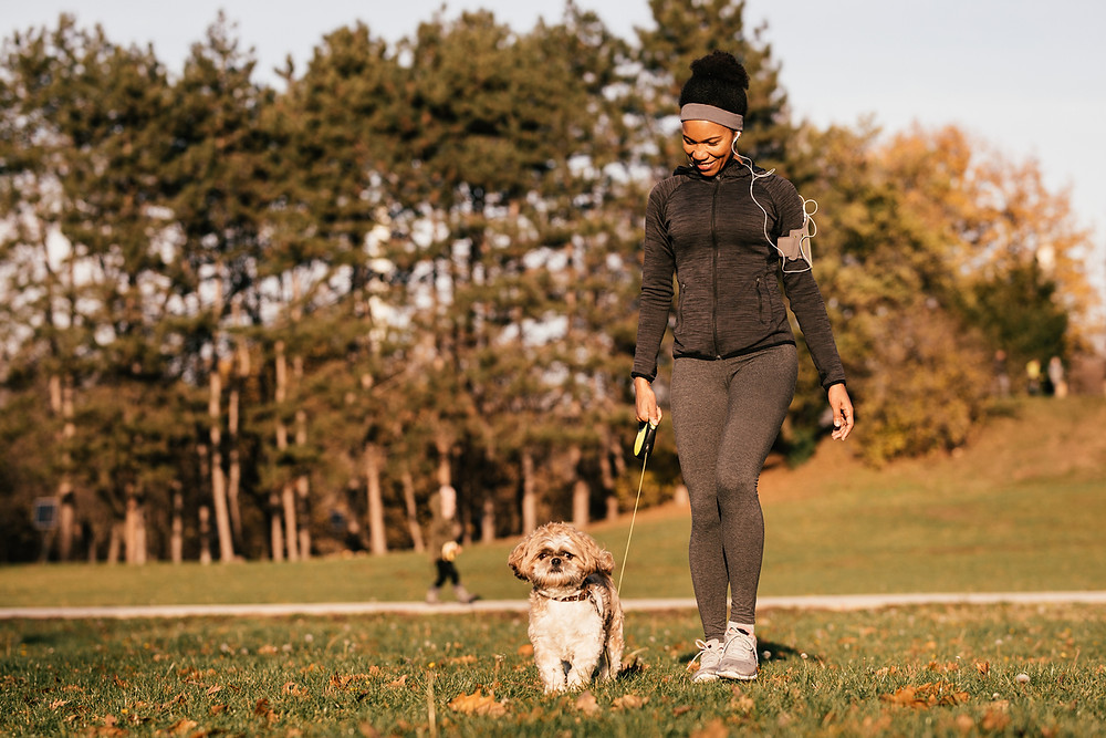 woman walking dog outside for exercise and stress relief