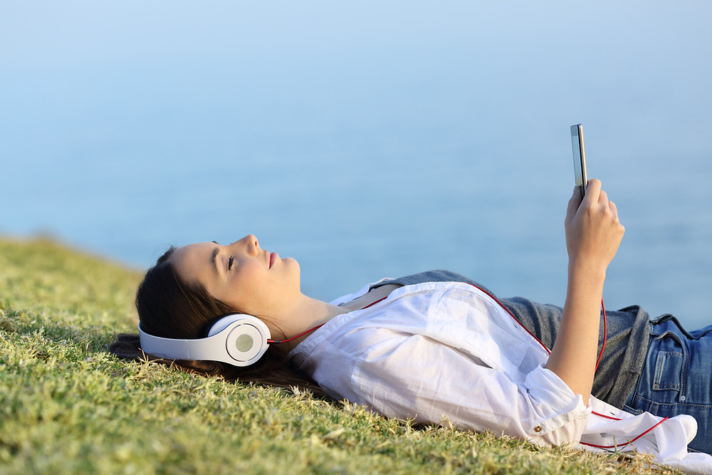 Young woman laying outside on grass by the water closing eyes listening to mindfulness app or guided meditation on phone with headphones