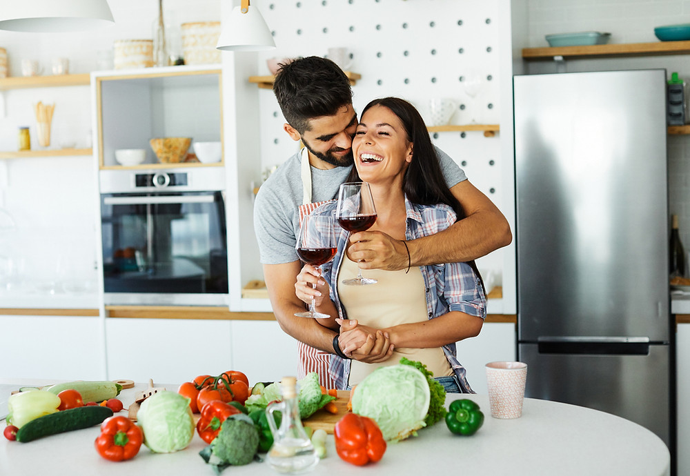 Young couple happy in love cooking in kitchen healthy with red wine