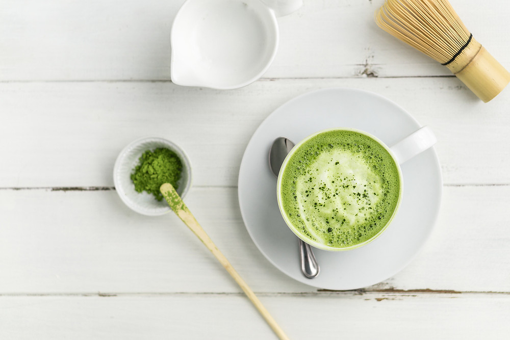 Picture of matcha latte with bamboo wisk (chasen), milk and matcha powder
