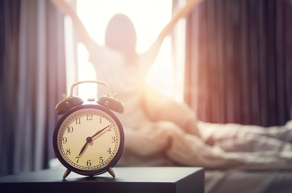 alarm clock with woman happily rising out of bed on sunny morning