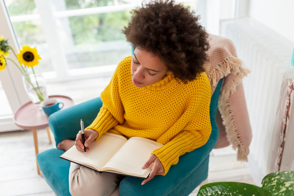 young woman writing daily affirmations in journal; self care