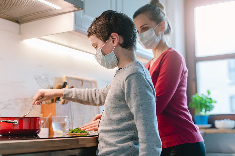 mom and son home cooking during pandemic wearing masks