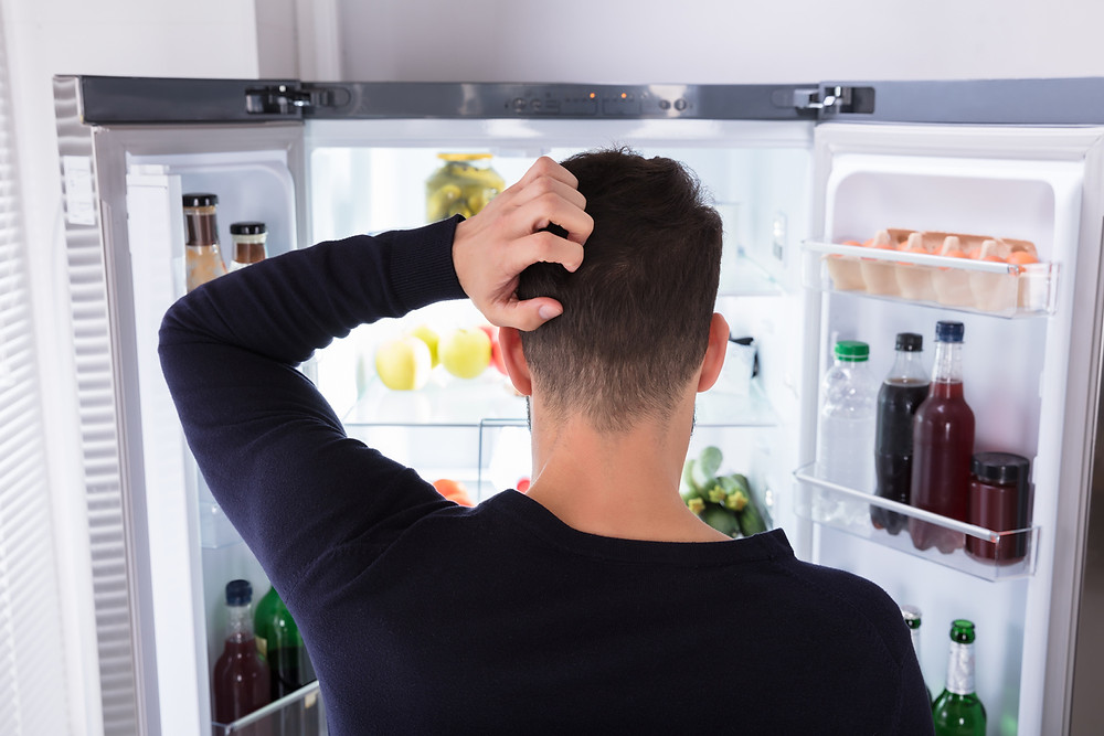 Young man looking in the fridge confused about what to eat for his diet