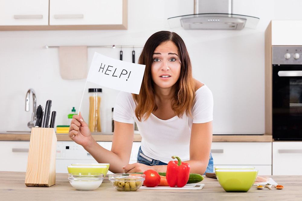 Young woman about to cook in kitchen asking for help deciding what is healthy to eat.