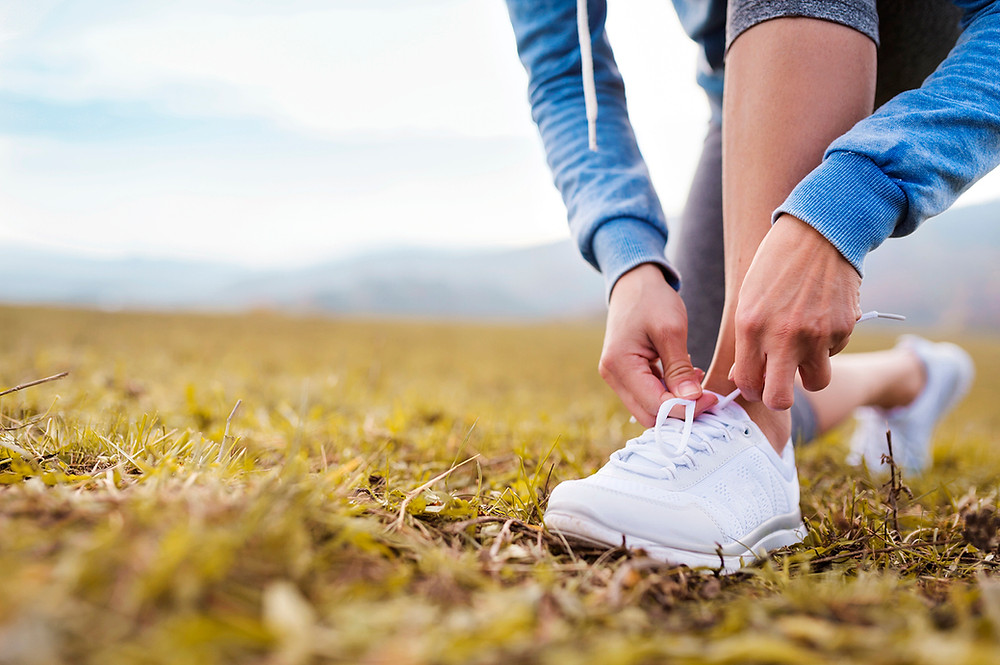 woman tying shoes to go for a walk in nature