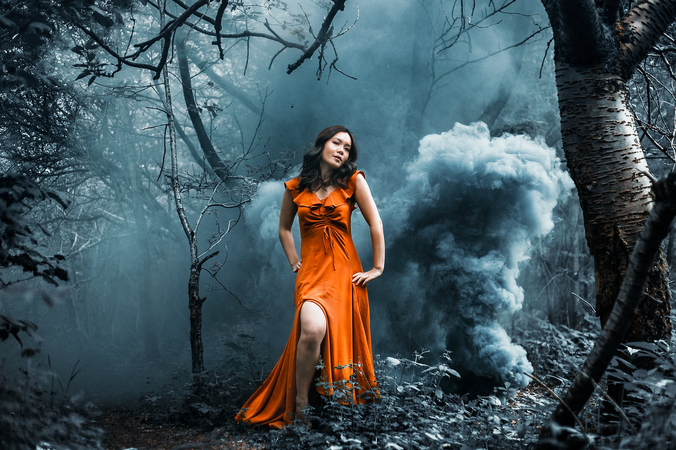 A woman stands alone in a forest in Manchester surrounded by a blue smoke grenade
