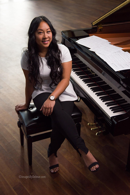 Jessica sitting at a grand piano