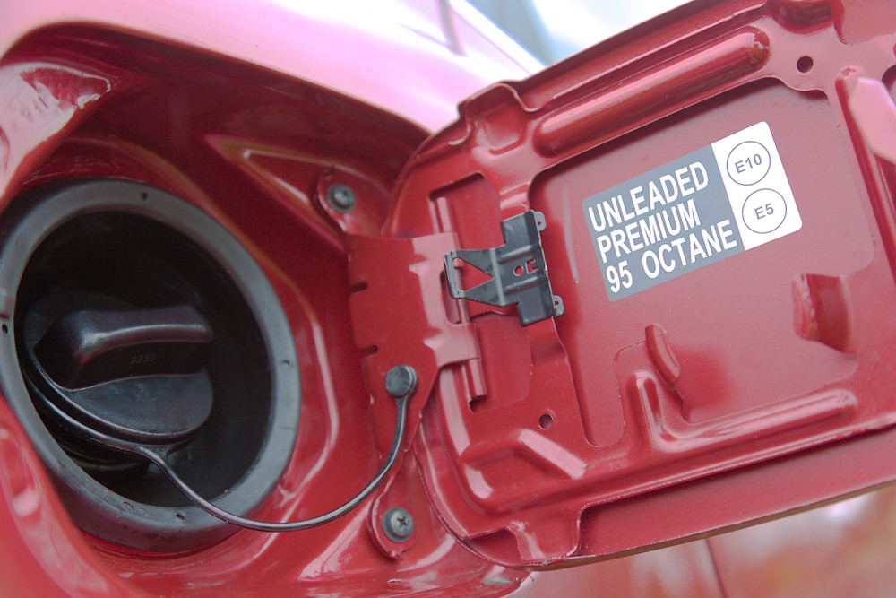 Fuel cap of a red car showing E10 and E5 petrol unleaded information.