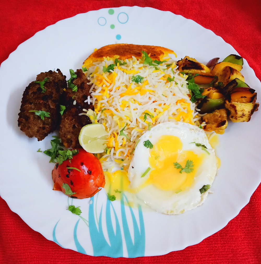 Chelo-Kabab is served with the basic Iranian meal accompaniments, in addition to grilled tomatoes on the side of the rice, and butter on top of the rice.