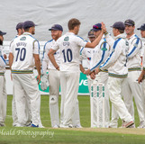 Coad congratulated by colleagues for taking first pink-ball YCCC County Championship wicket.