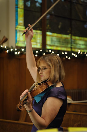 Kathy conducting violin recital.