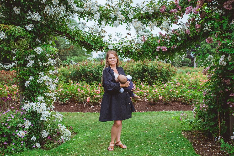 breastfeeding mother in a rose garden