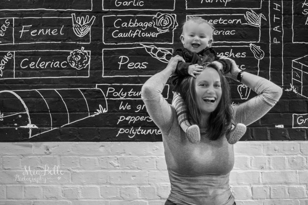 a baby on her mother's shoulders messing up her hair in a black and white image
