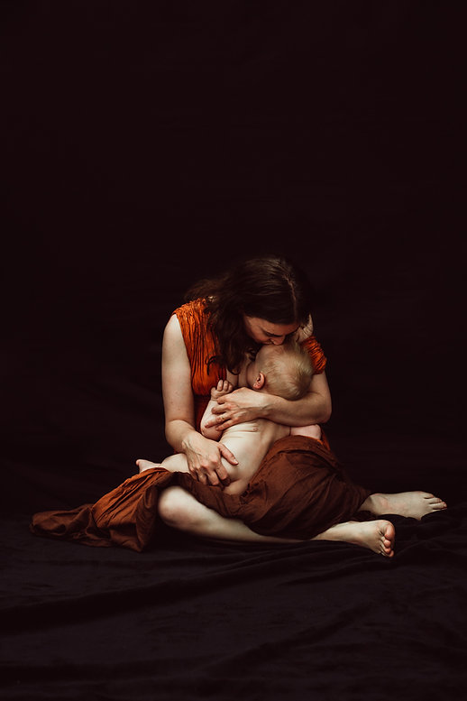 a mother kissing her baby while he breastfeeds