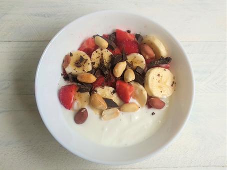 Bol de yogur con fruta, cacahuetes y chocolate.