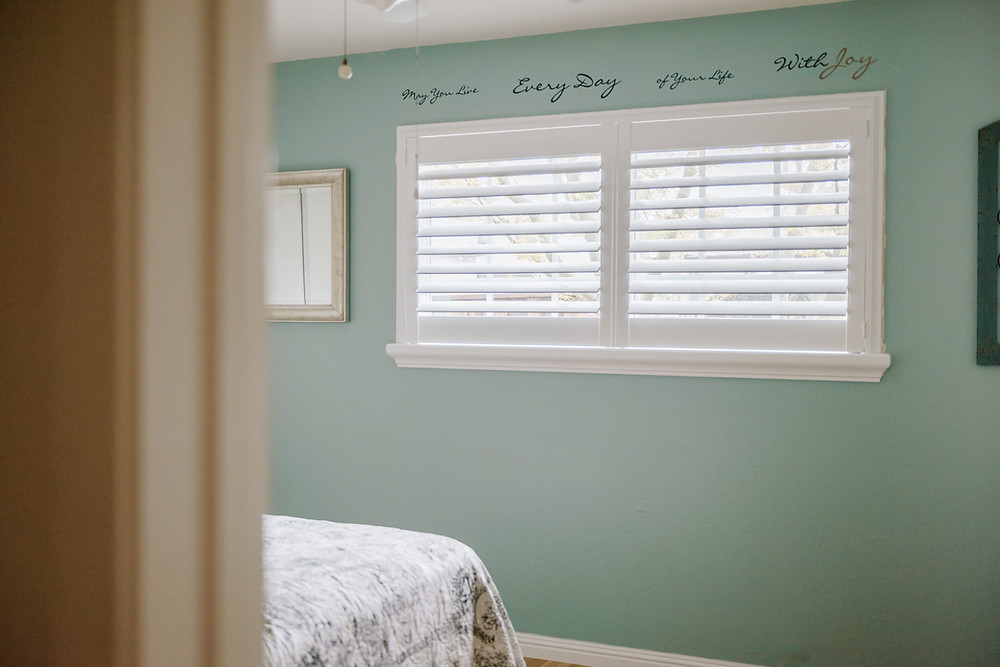 Light enters a room painted a sea-green color. The window has a double panel shutter mounted into the frame.