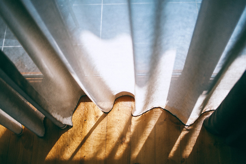 White sunlight streams through white sheer curtains, casting midday shadows on the wood floor.