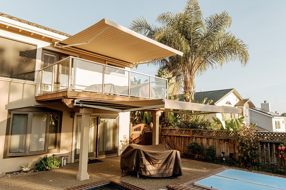 Dual SunSetter awnings are mounted to a two-story home. The upper awning shades a generous balcony from the golden light of sunset, while the lower awning shades the patio. A fluffy palm tree is in the background, overlooking the pool.