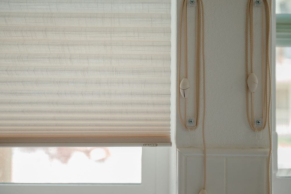"""""""After"""" photo of the kitchen window shades. These are corded shades, and the cords are stored by looping them over two vertically-mounted anchors that will keep them from cluttering the counter."""