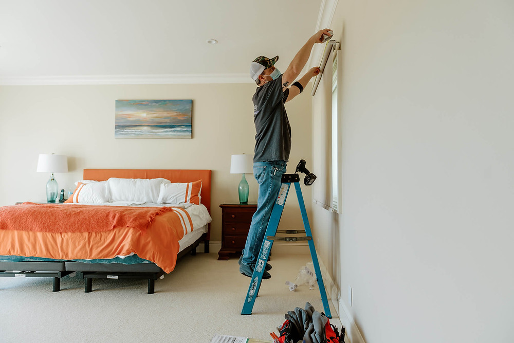 Window-ology installer, Ed, perches on a short blue ladder to measure a beige window roller shade. His drill is balanced on top of his ladder, and there is a queen bed to his left, covered in orange-accented bedsheets and pillows.