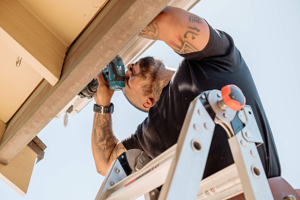 A Window-ology installer stands on his ladder and cranes his neck for a better view of the screws he is securing with a drill.