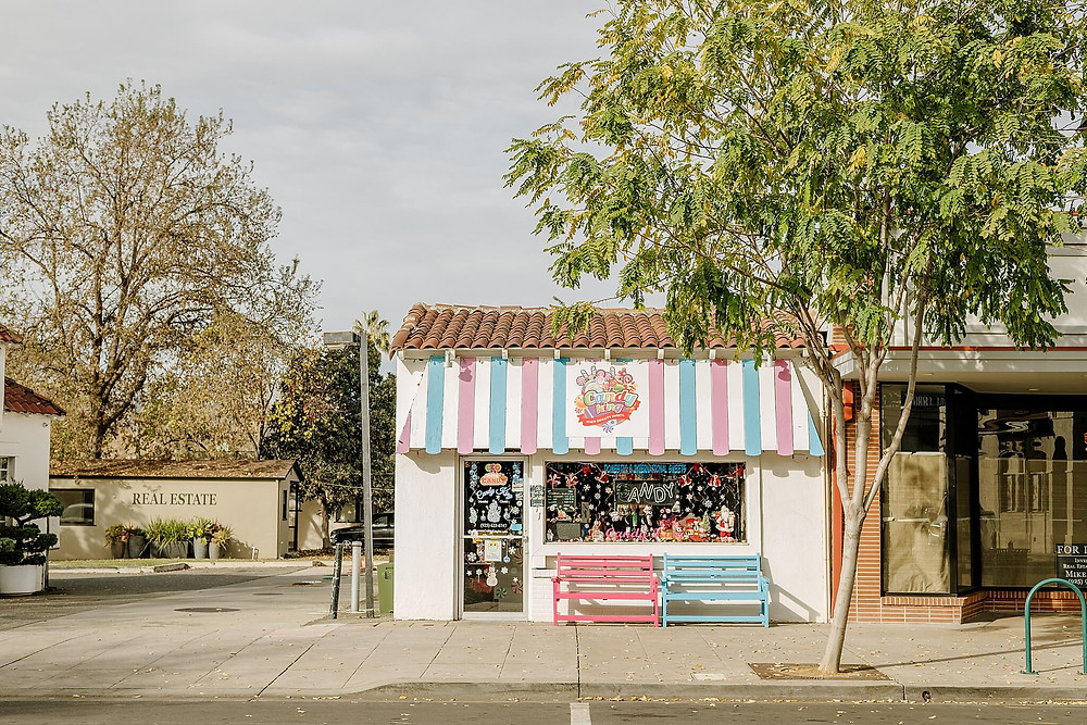 On a bright winter day, sunshine hits the happy blue and pink striped awning of Candy King, a local candy shop in downtown Pleasanton. Two cheer fun pink and blue benches sit just outside the door.