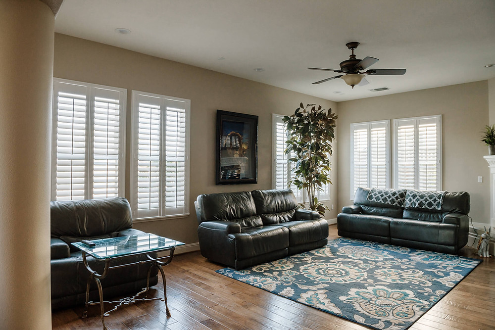 Three dark leather couches form an L shape in a living room. The windows are covered by white plantation shutters. A potted tree sits in the back left corner and a large, framed painting of a lion hangs on the back wall above the middle couch.