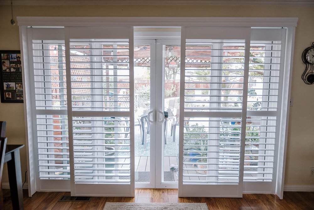 The panels of a bypass shutter sit on either side of the sliding glass door. The slats are open, allowing light to enter the room.