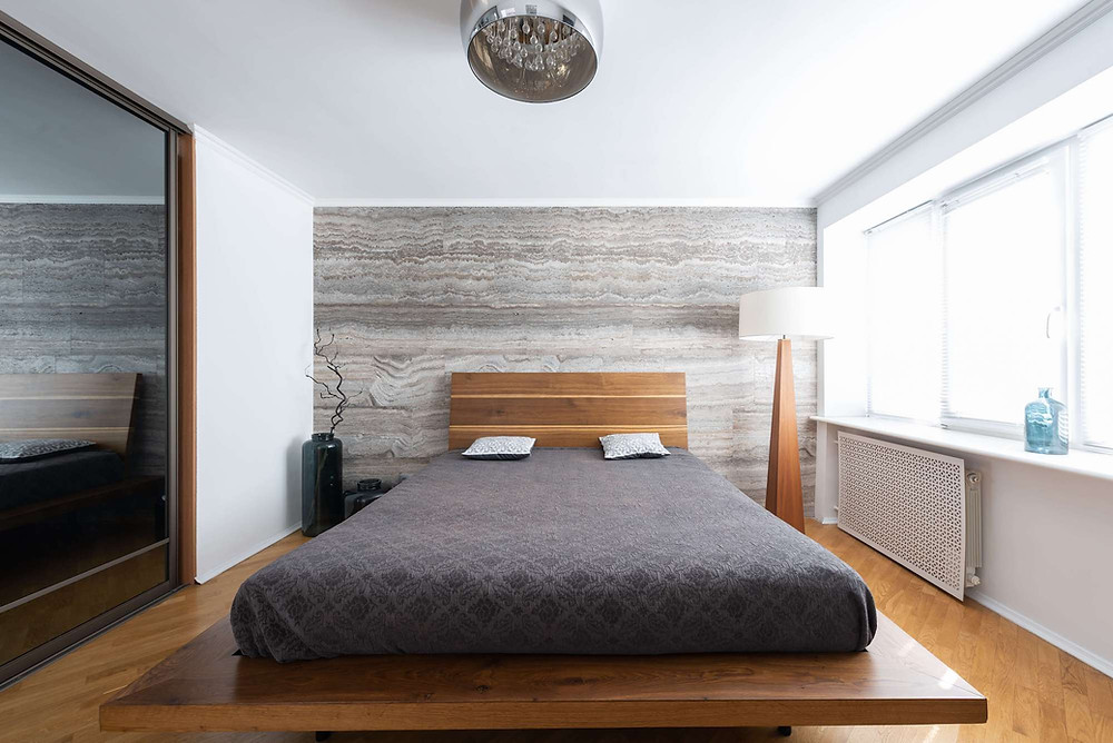 Minimalist room with king-sized bed on natural wood frame. On the left is a wall entirely taken up by a mirror, which reflects the light from the window along the opposite wall.