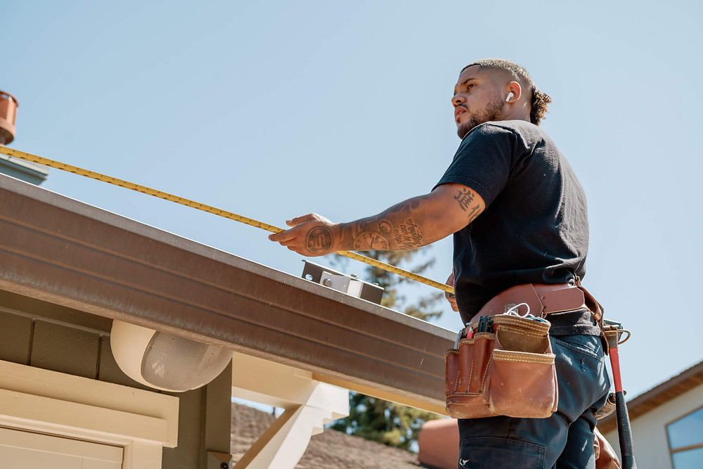 A Window-ology installer measures the length of the roof where he will install the awning.