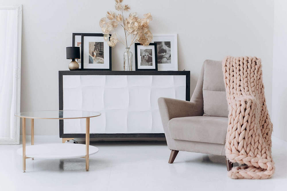 Huge pink knit blanket is draped over a beige chair. A console stands against the wall behind it with picture frames and a dried plant. On the left is a glass and gold round coffee table.
