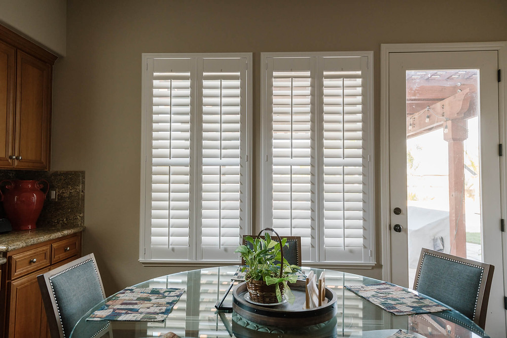 Two windows in front of a round glass dining room table feature plantation shutters with split tilt wands.
