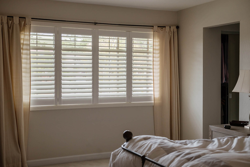 A long window features white composite shutters with invisitilt. The plantation shutters are layered by creamy curtains on either side of the window.  A bed with a mussed comforter is in the foreground.