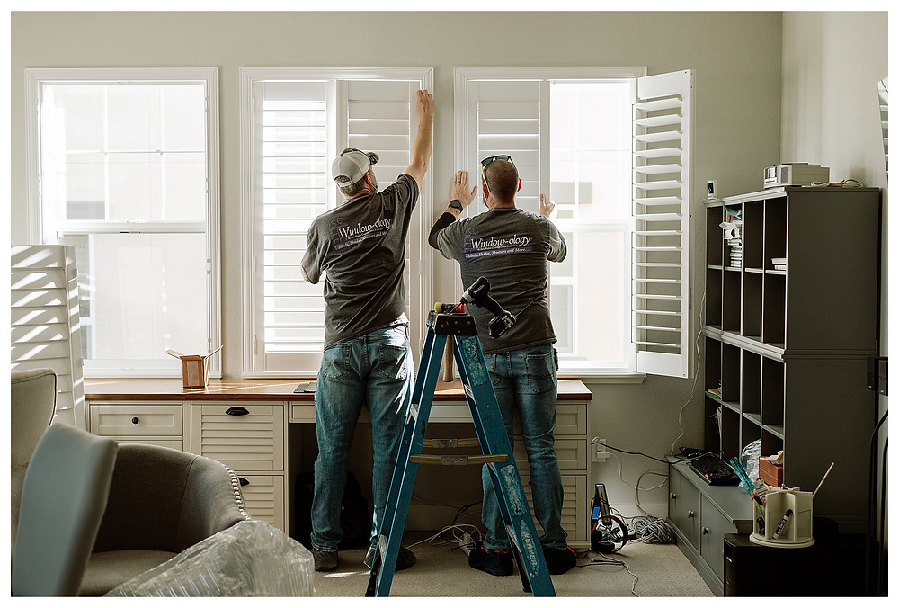 Two Window-ology installers stand on either side of a blue ladder, carefully placing pins into the hinges of the window shutters.