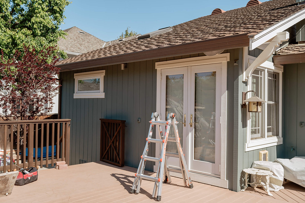 A short ladder stands on a wooden deck on a back patio. Windowology installers will mount an awning to the shingled roof of the home, shading a set of French doors.
