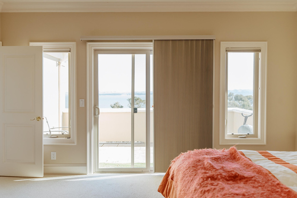 The camera faces a sliding glass door straight on. A tan slide-vue shade covers the right half of the door, which leads to a balcony overlooking the San Pablo Bay in San Rafael, California. A queen bed is in the right foreground, covered with a fuzzy orange bedspread.