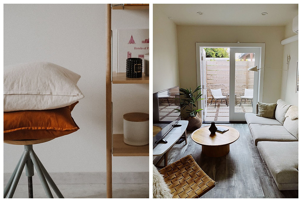 Left: Two plump pillows, one white linen, the other rusty orange, sit on a round wooden stool next to a bookshelf. The bookshelf holds assorted candles and books. Right: We face a French door with one panel opening onto the patio. The room is a cheerful butter yellow. A beige couch sits against the right wall, opposite a flat-screen TV on the left. A simple, round, wooden coffee table sits in the middle of the room. A leafy green plant is in the left corner by the TV.
