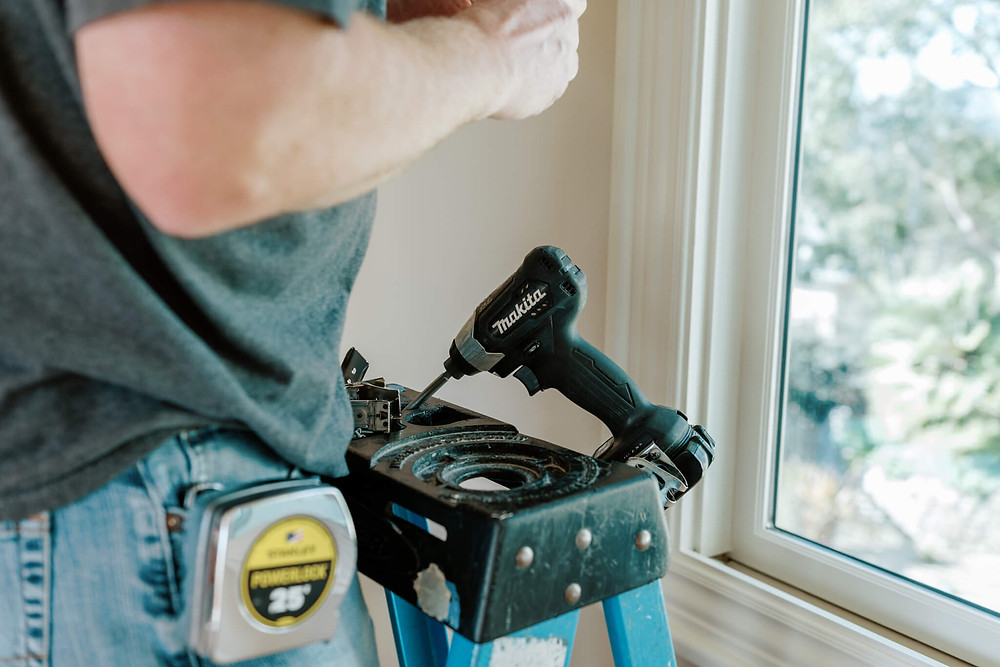 A ladder stands next to a window, with an electric drill perched on top. Window-ology installer, Ed, fiddles with brackets before mounting them to the wall.