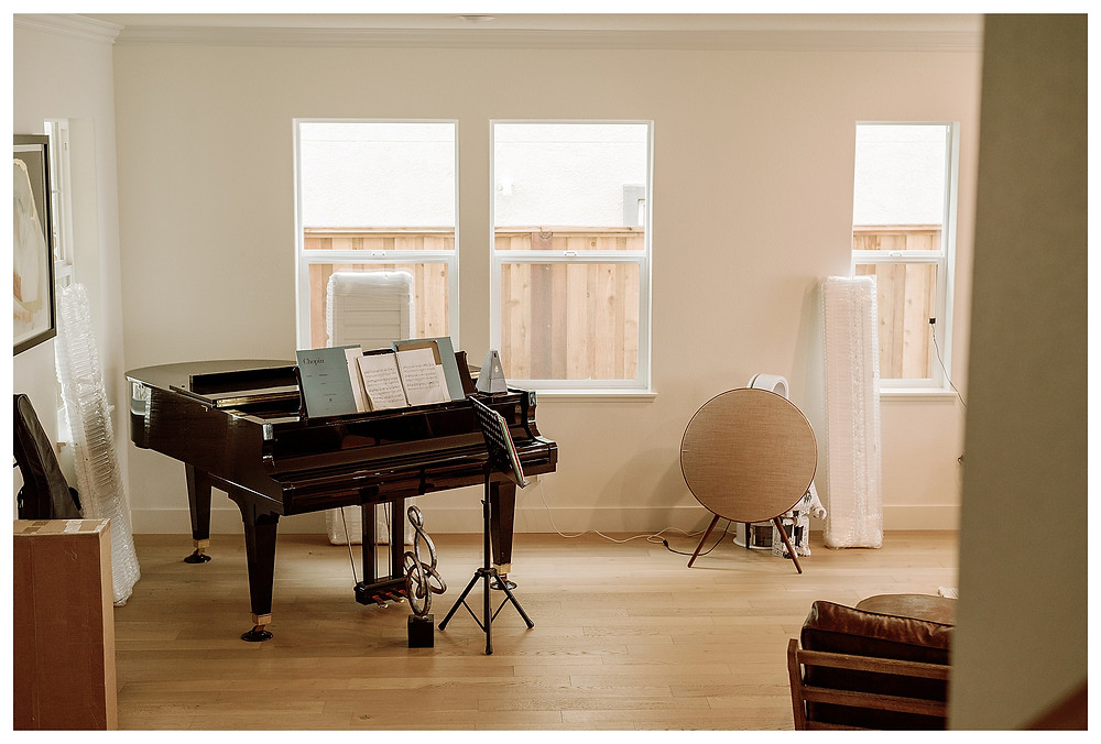 A black grand piano sits in the corner of the living room, against three windows that wait for their shutters.
