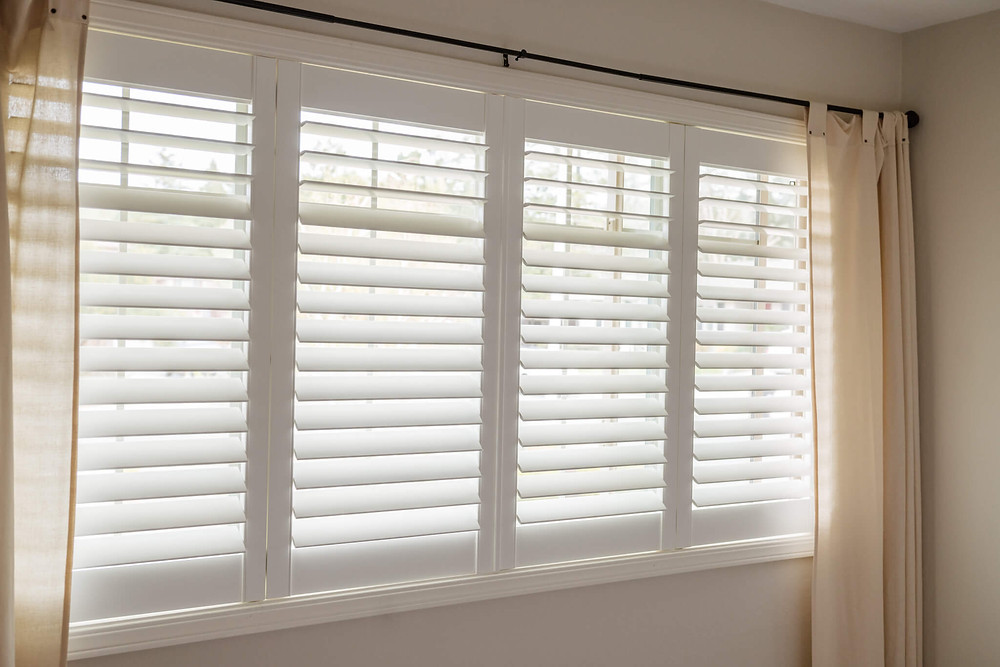 A long window features white composite shutters with invisitilt. The plantation shutters are layered by creamy curtains on either side of the window.