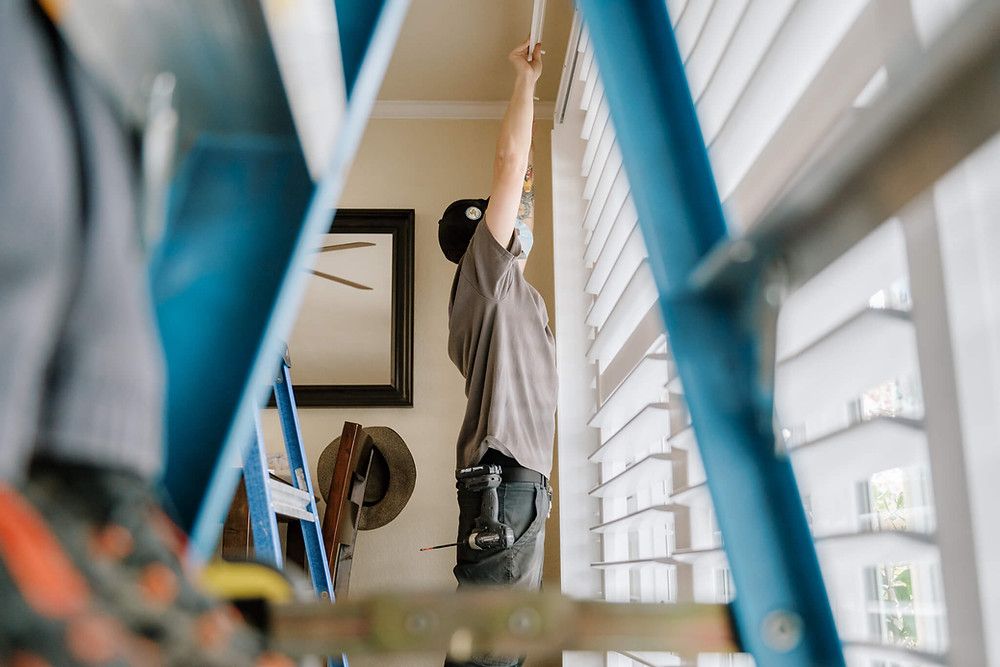 A Window-ology installer hoists a bypass shutter frame to the top of a sliding glass door. He is framed by the legs of a blue ladder between which the viewer looks.