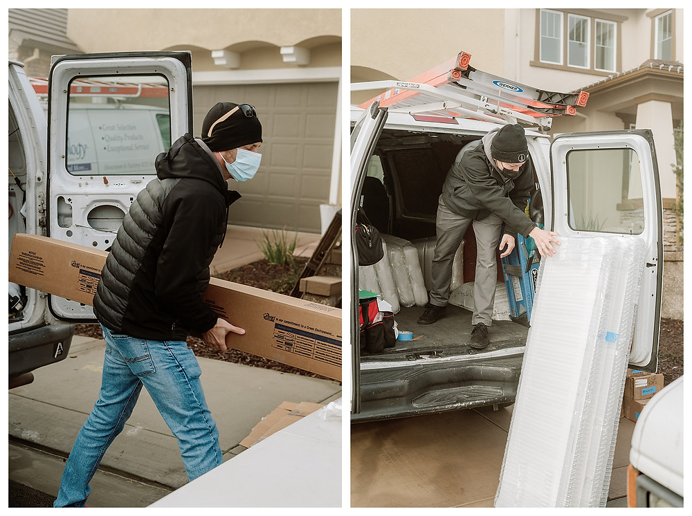 Left: A Window-ology installer carries a long brown box containing window shutters out of a large white company van. The installer is wearing a black beanie, sunglasses and a down jacket with jeans and a face mask. He is going to put the package down on the plastic table in front of him. Right: A Window-ology installer lifts bubble-wrapped shutters out of the company van, propping them up against the back van door.