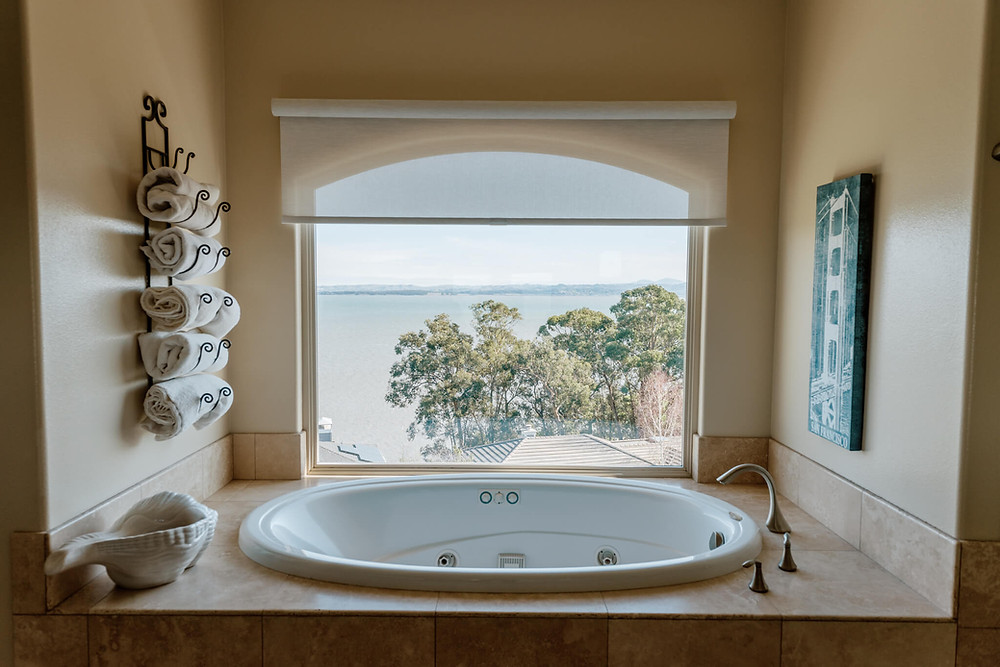 A large, arched bathroom window provides a view onto the sunny San Pablo Bay in the San Francisco Bay Area, California. The window is located next to a bathtub and is partially covered by a sheer white roller shade. A rack of fluffy towels hangs on the left wall.