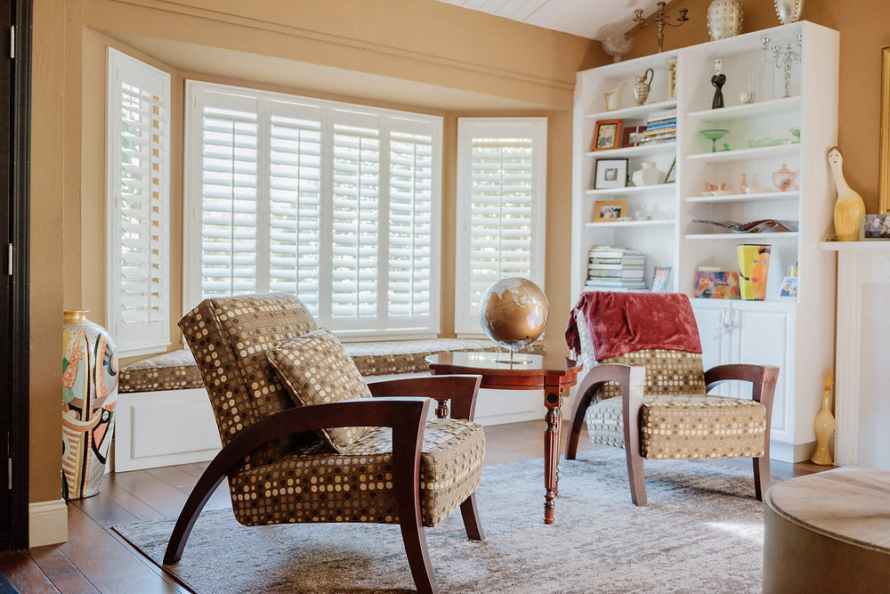 Setting: A living room. Plantation shutters are mounted into the tryptic of windows, which feature a window seat. The pattern of the window seat matches those of the two chairs in front of it, one sitting on either side of a round mahogany coffee table. There is a copper globe on top of the table.