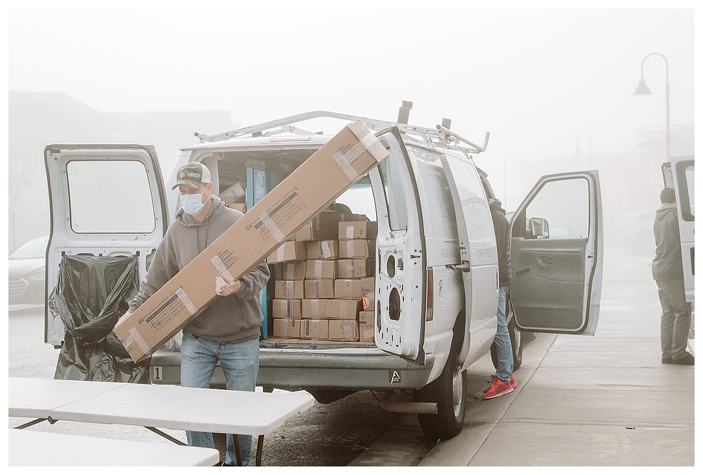 A Window-ology installer carries a long brown box containing window shutters out of a large white company van. The installer is wearing a baseball cap and sweatshirt with jeans and a face mask. He is going to put the package down on the plastic table in front of him.
