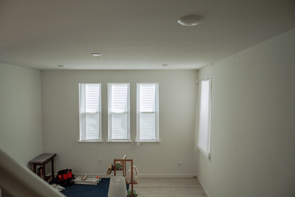 """A """"before"""" photo of the living room where Window-ology installed new cellular shades. The three narrow windows are covered by temporary shades, which look like cell shades but are made of paper."""